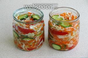 На дно стерилизованных банок ёмкостью 1 л положить по 1 лавровому листочку, дальше уложить овощную массу, а сверху влить по 2 столовые ложки растительного масла и 1 столовой ложке уксуса.