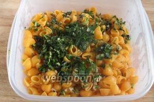 Добавьте к макаронам ароматное масло с чесноком и тимьяном, нарубленную зелень и перемешайте.