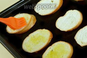Багет разрезаем по диагонали на кусочки толщиной 13-15 мм, смазываем оливковым маслом с помощью кисточки и подрумяниваем до золотистого цвета в духовке.