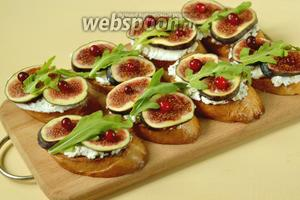 Раскладываем на поверхности рикотты ломтики свежего инжира, украшаем листочком рукколы и ягодами клюквы. Для подачи выкладываем на большое плоское блюдо.