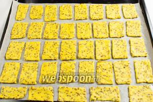 Разложить заготовки печенья по пергаментной бумаге на противень. Поставить его в горячую духовку. Выпекать при температуре 190 °C в течение 15 минут до золотистого цвета.