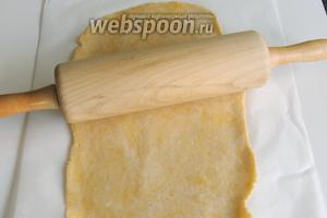Тесто раскатаем на пекарской бумаге в овал шириной около 20-25 см и длиной 40 см. Если будет тесто прилипать к скалке, то немного припудрить мукой.