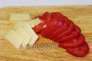 Тем временем, нарезать кружками помидор и тонкими ломтиками сыр.