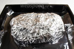 Тщательно завернуть мясо в фольгу. Выложить мясо в фольге на противень. Поставить в заранее разогретую до 200°С духовку. Запекать мясо в течение 2 часов. Потом развернуть фольгу и запекать мясо ещё в течение 30 минут до румяности. В общей сложности 2 часа 30 минут. Но, если у Вас кусок свинины другого размера, то Вы можете самостоятельно рассчитать время приготовления: если 1 кг мяса — достаточно будет 1 часа 30 минут, из них 1 час запекаем при температуре 200°С, остальные 30 минут разворачиваем и запекаем ещё 30 минут при температуре 200°С. Но учтите, что есть особенности в духовке, то есть после первых 20 минут, когда мясо будет открытым, следите за ним.