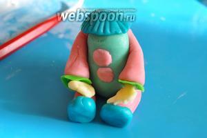 Тельце сделаем из мастики другого цвета, прикрепим из маленьких шариков пуговки. Закрепим конечности. Манишку сделаем из кружочка, край сделать рифленым просто прижимая нож.
