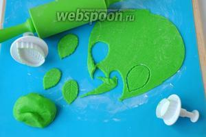 Из мастики зелёного цвета режем листики, если нет плунжера, вырезать ножом, и нанести разводы, слегка надавливая.