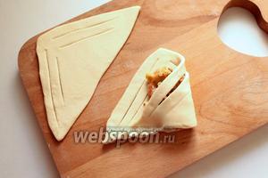 Раскатать треугольники со стороной 10 см, сделать по бокам надрезы. Для начинки положить одну столовую ложку яблок и посыпать измельчёнными, обжаренными орехами. Завернуть уголочки.