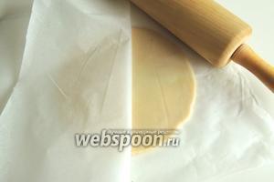 Раскатаем марципан между 2-мя слоями кулинарной бумаги или пищевой плёнки в круг диаметром, равным форме.