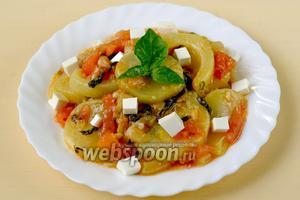 Выкладываем готовые кабачки в тарелки, добавляем кубики Фетаксы и листики базилика. Блюдо можно есть как горячим, так и холодным.