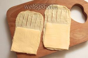 Раскатать тесто в форме прямоугольника толщиной 2-3 мм, смазать растительным маслом. На одну половину положить сыр, а на другой части сделать несколько надрезов.