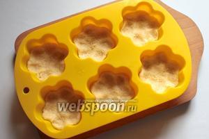 Разделить тесто на 12 кусочков, заполнить ими формы.