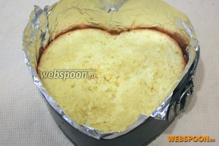 Подготовьте форму для торта. Обложите форму фольгой. На дно формы выложите первый корж и пропитайте его пропиткой.