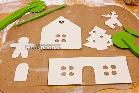 Раскатать тесто толщиной примерно 0,5 см. Теперь нам понадобятся предварительно вырезанные из картона части домика и декорации (см. описание к рецепту). Картонные формочки разложить на тесто и аккуратно ножом вырезать по контуру.