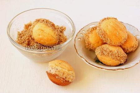 Соединить 2 половинки печенья, чтобы образовался орешек. Выступивший по швам крем обсыпать молотыми грецкими орехами.