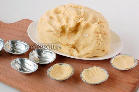 Отрывать от теста небольшие кусочки и наполнять им специальные металлические формочки для орешков, распределяя тесто по формочке.