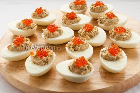 Фаршированные яйца можно украсить икрой и подавать на стол, выложив на листья салата с оливками.