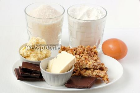 Для приготовления пирожного «Буковинский орех» нам понадобится сахар, мука, яйца куриные, какао, шоколад, масло, 100 г крема «Шарлотт», 200 г  грильяжа из грецких орехов .