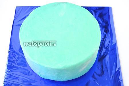 Манипуляции с мастикой и тортом лучше выполнять на ровной поверхности. Сбрызнуть торт из спрея немного водой, чтобы слегка увлажнить поверхность. Раскатать мастику в большой пласт, намотать на скалку и наложить на торт. Разровнять, выровнять угол и боковины, срезать излишки по низу.