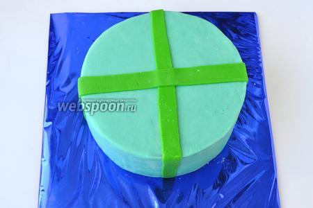 Раскатать из зелёной мастики ленты и наложить на торт крестом, под ленты кисточкой нанести немного сахарного сиропа для фиксации.
