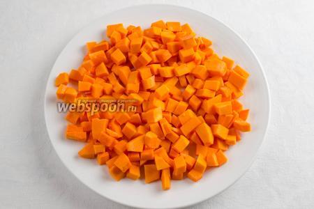 Тем временем подготовить овощи. Тыкву вымыть. Почистить. Нарезать кубиком.