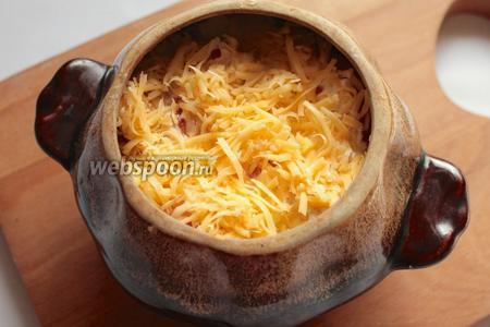 Натереть сыр на средней тёрке и заполнить горшочки.