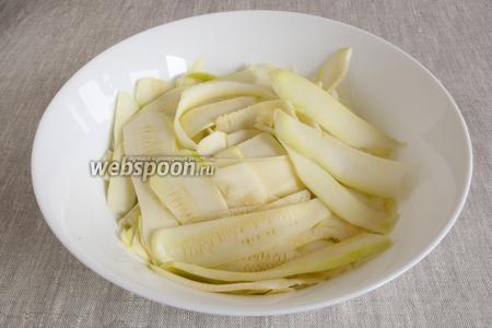 При помощи ножа для овощей нарезать очищенные кабачки лентами. Посолить, оставить на 30 минут, выделившийся сок слить.