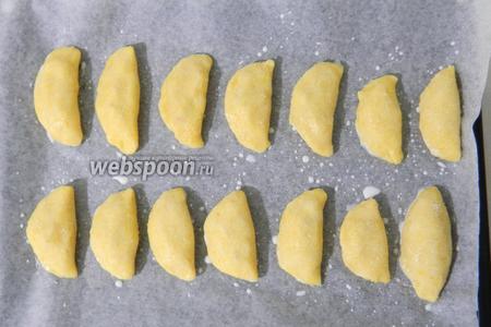 Пирожки выкладываем на противень с пергаментной бумагой. Смазываем молоком и обильно посыпаем сахаром для хрустящей корочки.