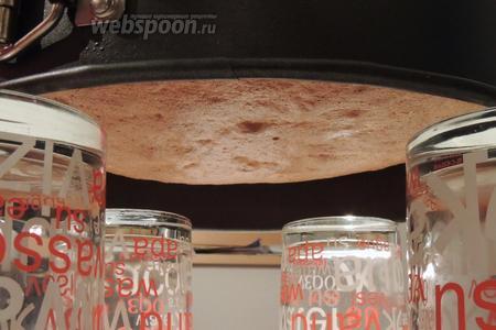 Вынимаем из духовки и не теряя ни секунды, ставим форму «вниз головой» на 4 стакана. Остудим в таком положении. У нас получится бисквит с идеальной поверхностью (без выпуклостей и впадин).