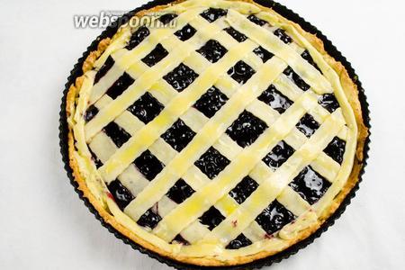 Вторую часть теста раскатать и нарезать полосками. Закрыть начинку пирога полосками в виде решётки. Смазать полоски желтком. Поставить форму в горячую духовку. Выпекать в течение 25-30 минут при температуре 180 °C.