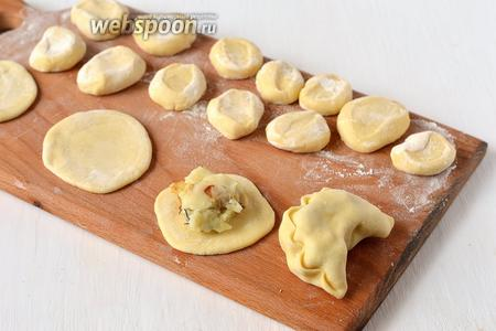 Из кусочков раскатать лепешки толщиной 0,3 см. На лепёшку выложить столовую ложку начинки и сформировать вареник.