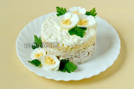 Снимаем кольцо, украшаем цветочками из белка и желтка, добавляем листочки петрушки. Порционный салат можно подавать сразу, в общем блюде — стоит подержать в холодильнике для пропитки.