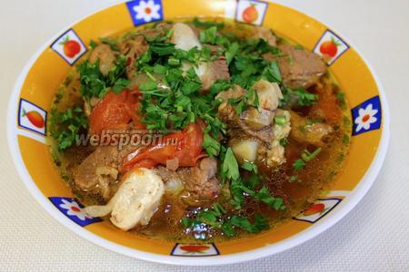 В глубокую пиалу налить бульон с мясом, добавить толчёный чеснок и посыпать зеленью.