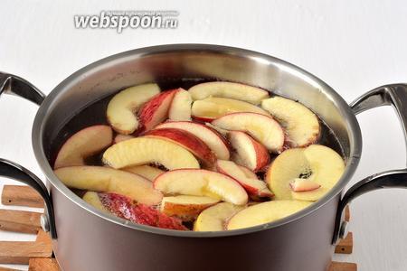 В сыпать яблоки в кипящий сироп. Убавить огонь и варить 3 минуты.