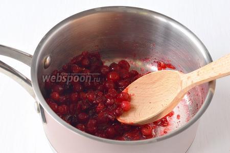 Размять ягоды деревянной ложкой.