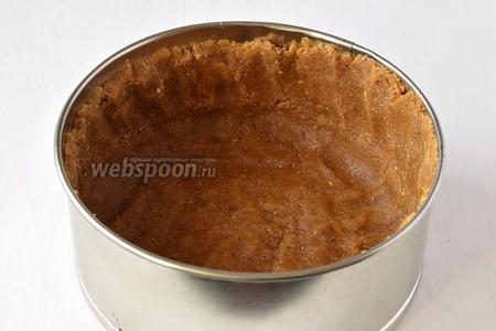 Форму диаметром 16 см выложить кулинарной бумагой. Сформировать из массы дно и бортики.
