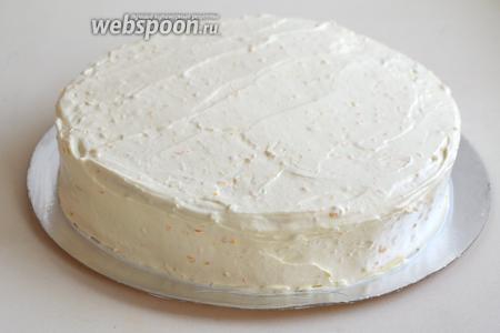 Обмажьте бока и верх торта кремом, разгладьте поверхность кулинарным шпателем.