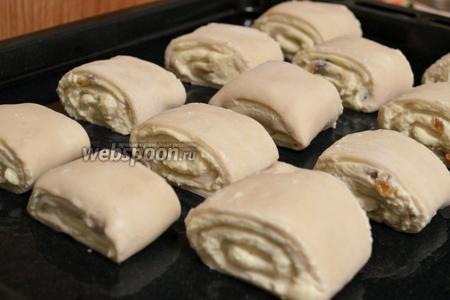 Рулет нарезать на булочки размером примерно 3-4 см. Переложить на противень, смазанный маслом.