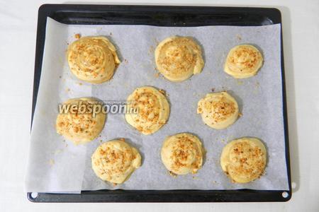 Переносим их на противень с пергаментной бумагой. Слегка придавливаем их, смазываем яйцом и посыпаем орешками.
