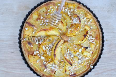 На пирог высыпать резаный миндаль и нанести мёд с помощью ложки.