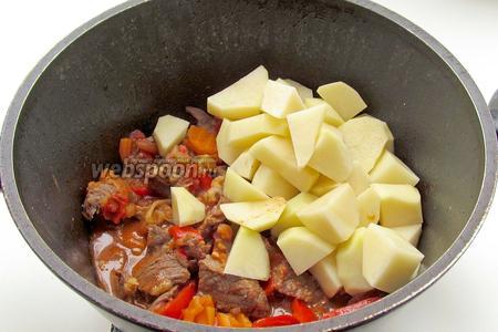 Добавляем картофель в казан к овощам. Перемешиваем, присаливаем.
