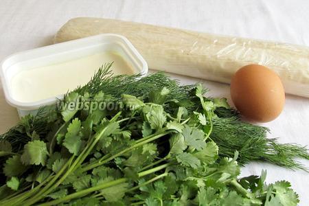 Нам понадобятся слоёное тесто, сыр фета или мягкая кисловатая брынза, яйцо для смазки, зубчик чеснока, разная зелень, кунжут, 1 столовая ложка растительного масла и смесь хмели-сунели.