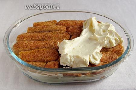 Аналогично выложить второй слой печенья и снова смазать кремом.
