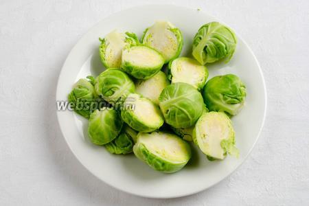 Подготовить овощи. Брюссельскую капусту вымыть. Срезать край кочерышки. Очистить от крайних лепестков кочанчики. Нарезать на половинки.