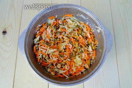 Положить в казан нарезанную морковь и лук, можно использовать для моркови тёрку.  Обжарить овощи с морепродуктами.