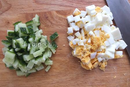 Нарежьте огурцы и яйца кубиками.