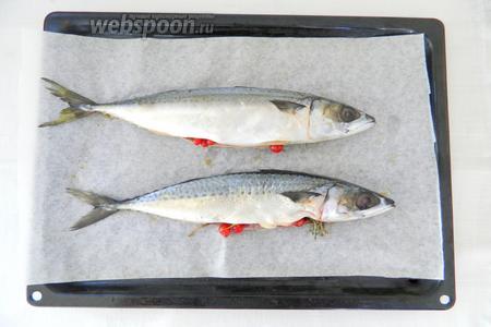 Перекладываем рыбу на противень с пергаментной бумагой. В брюшки укладываем тимьян, красную смородину. Зубчики чеснока раздавливаем широкой стороной лезвия ножа и так же кладём внутрь брюшек.