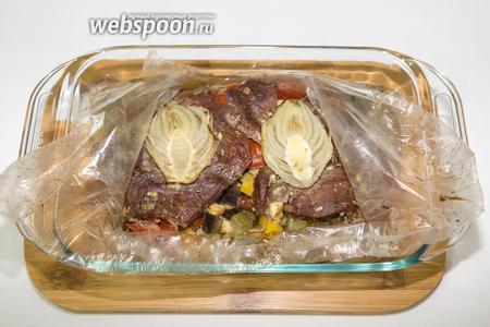 По истечении указанного времени вынимаем форму с пакетом для запекания. Пакет разрезать. Блюдо готово. Подаем на общей тарелке как самостоятельное блюдо.  Выкладываем овощи, сверху — мясо. Можно сбрызнуть уксусом.