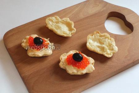 На сыр положить икру или кусочки филе слабосолёной сёмги. Украсить черной жемчужиной — оливкой.