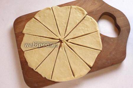 Часть теста раскатать в круг на слегка смазанной поверхности, разрезать на сегменты.