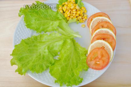 Сервируем тарелку. В мексиканских ресторанах подают такую курицу с початком варёной кукурузы, если её нет, воспользуйтесь консервированной. Выложим на тарелку листья салата, помидор и часть лимона, кукурузу.